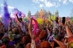 Participants dance and throw colored chalk during the Holi Festi